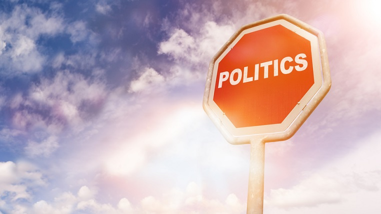 Politics, text on red traffic stop sign in front of cloudy blue sky with lens flares