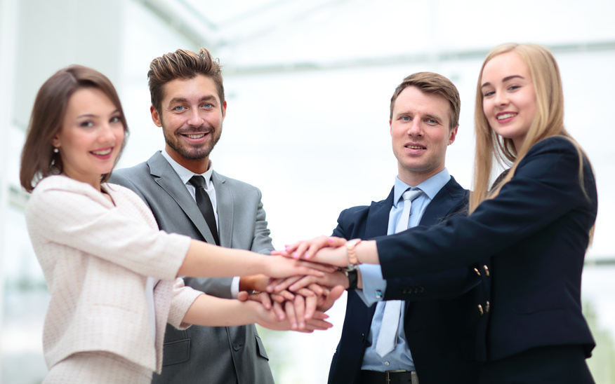 Group of business people putting their hands on top of each other.
